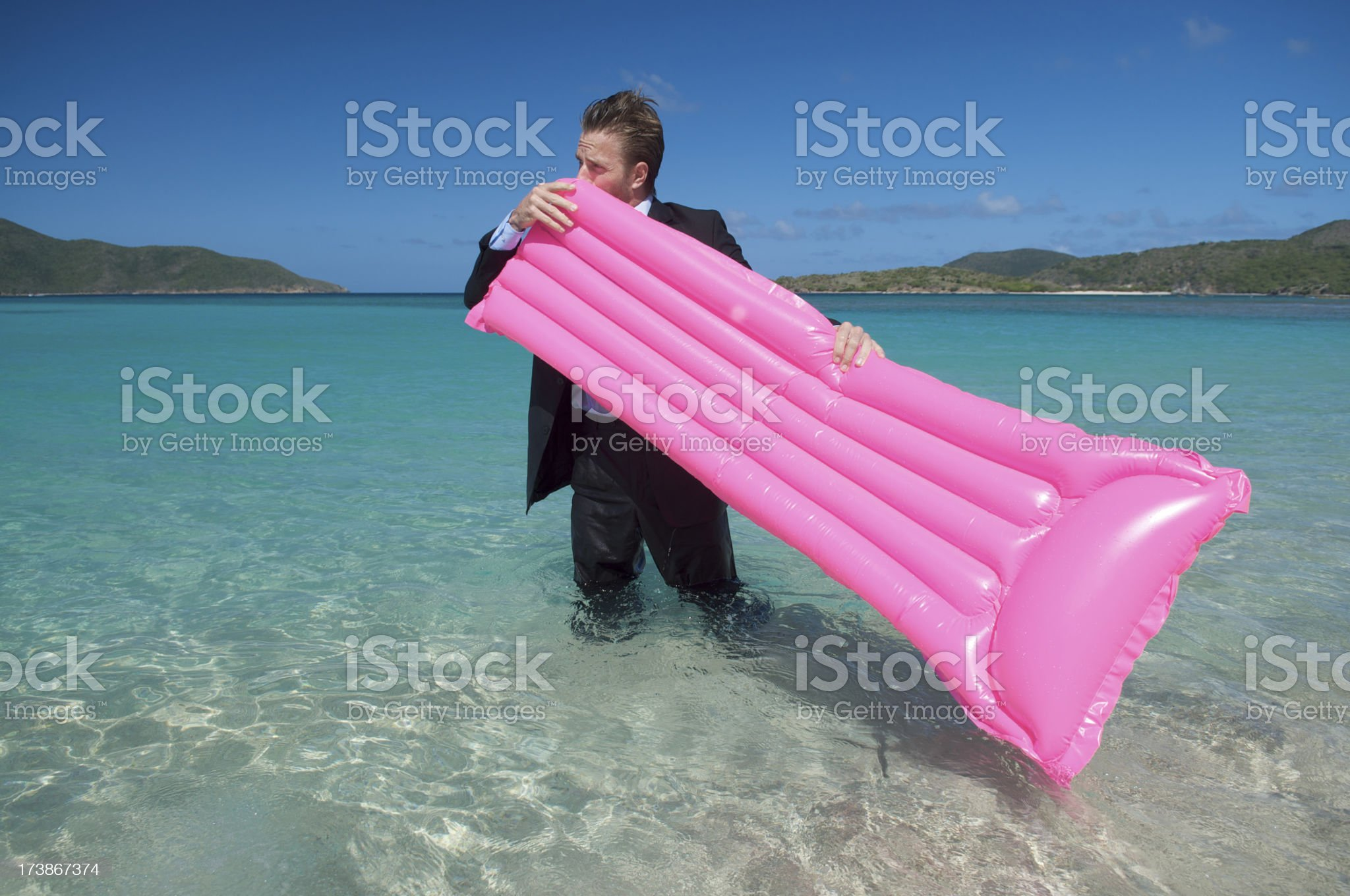 Businessman Blows Up Pink Lilo in Sea royalty-free stock photo
