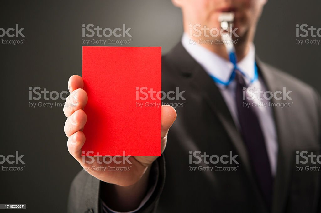 Businessman blows whistle and shows red card stock photo