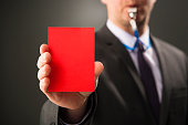 Businessman blows whistle and shows red card