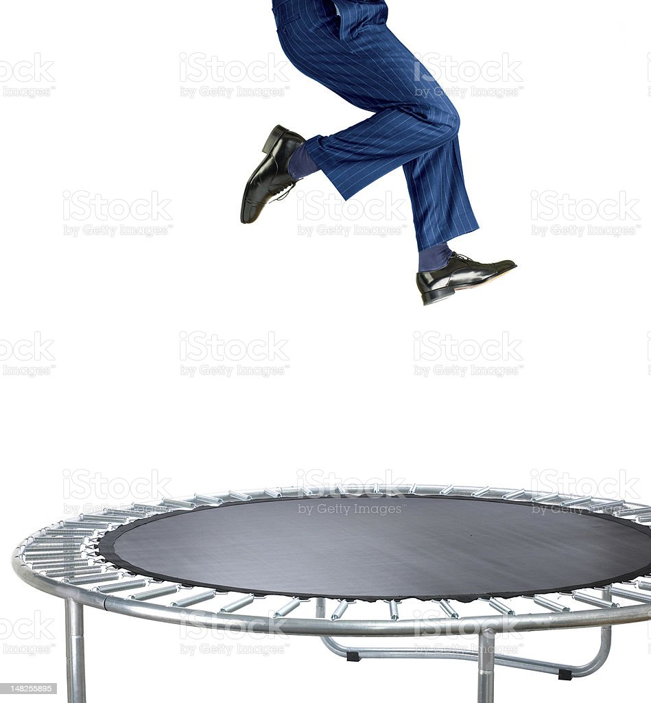 businessman bouncing on a trampoline against white stock photo