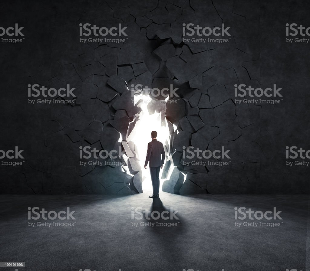 businessman breaks trough a wall stock photo