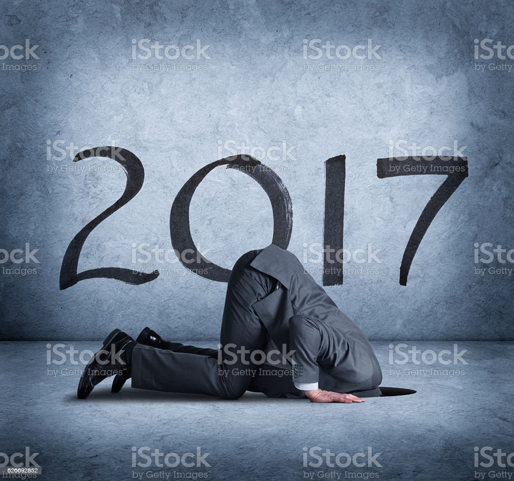 Businessman Burrying Head In Hole As 2017 Approaches stock photo