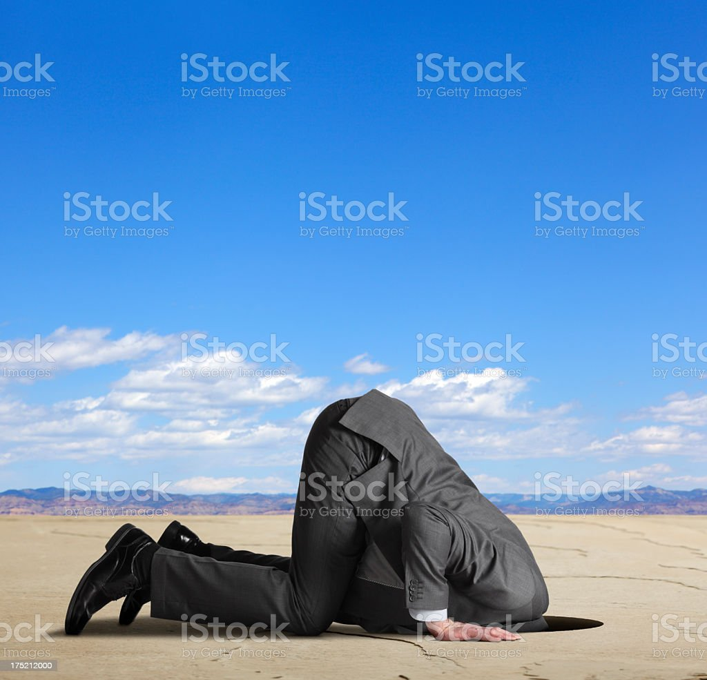 Businessman burying his head in the sand stock photo