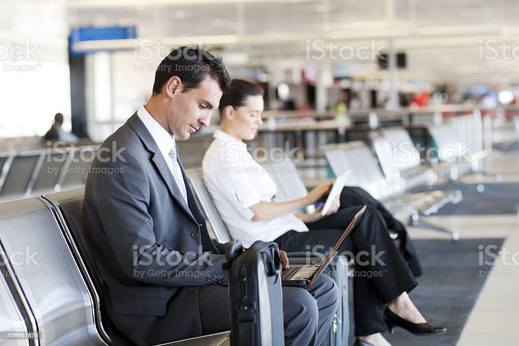 businessman businesswoman using laptop and tablet at airport royalty-free stock photo