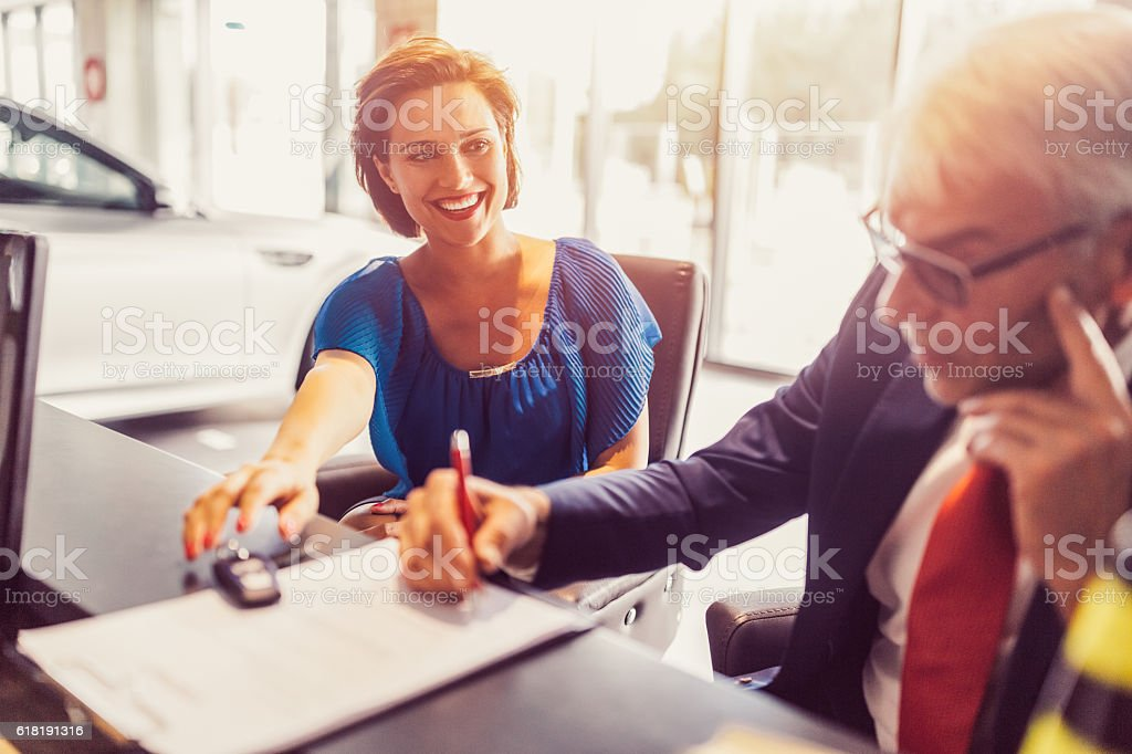 Businessman buying a new car for his wife stock photo