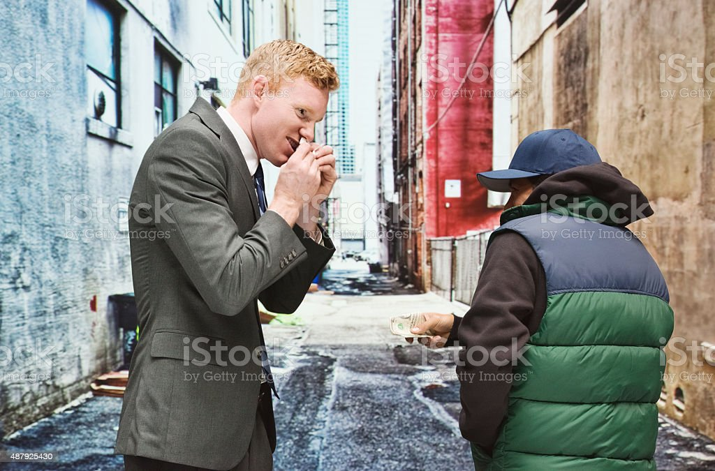 Businessman buying drugs from gangster stock photo