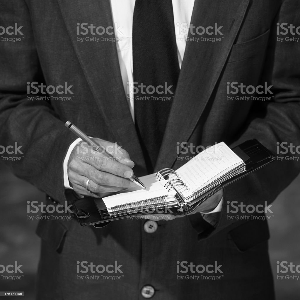 Businessman bw suit writing on his diary notebook stock photo