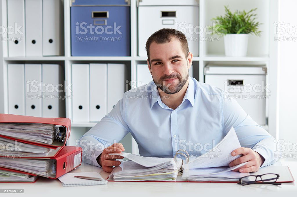 Businessman calculates taxes in office stock photo