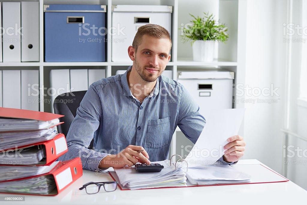 Businessman calculates taxes stock photo