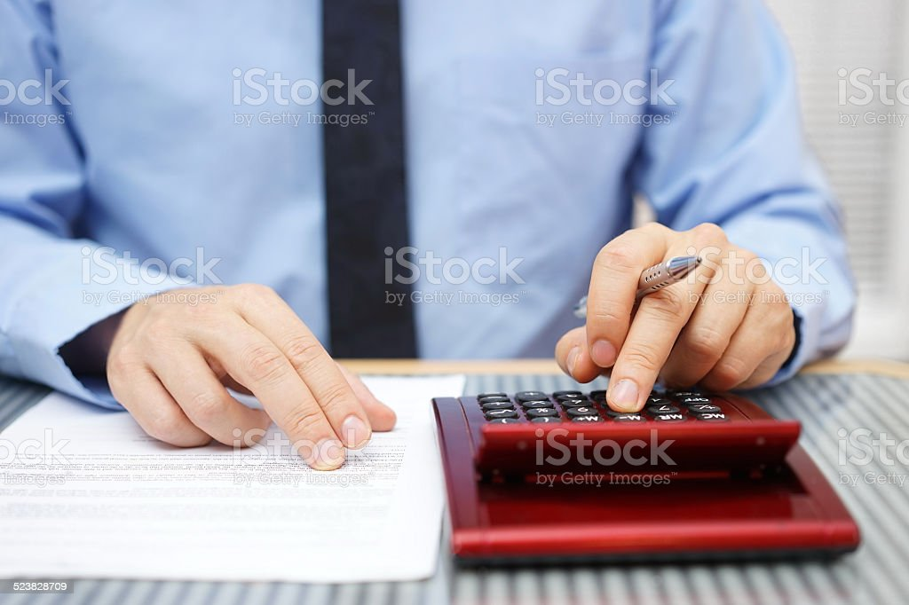 Businessman calculating  and checking articles of agreement stock photo