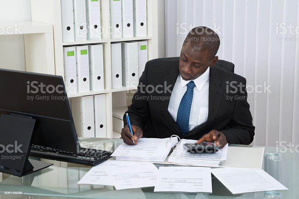 Businessman Calculating Finance Bills stock photo
