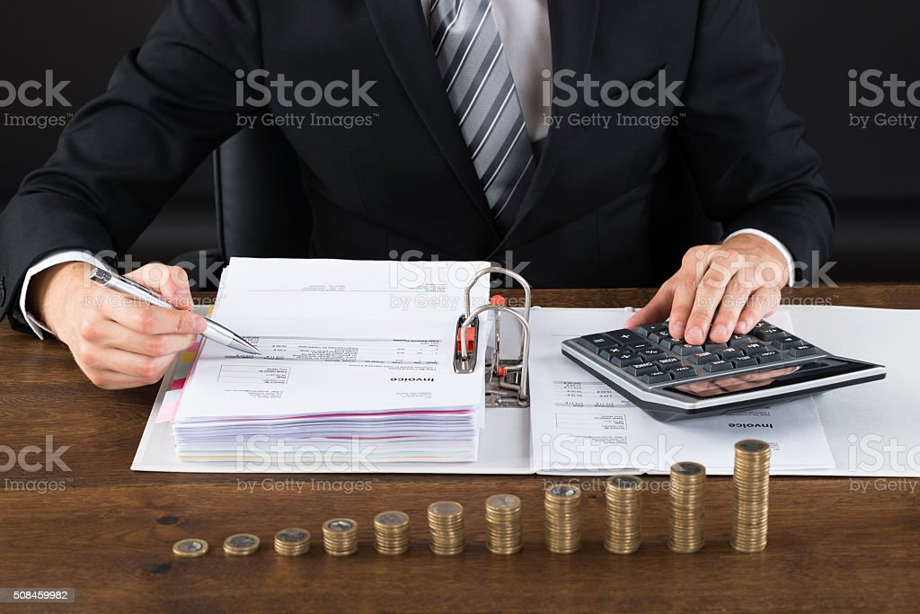 Businessman Calculating Invoice With Coins At Desk stock photo
