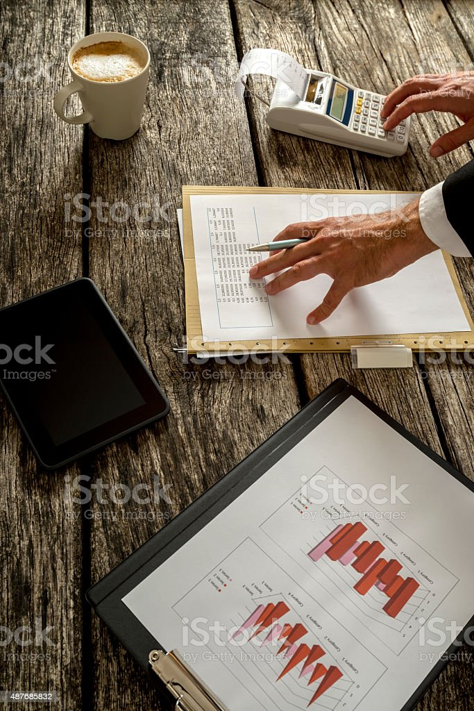 Businessman Calculating Sales on the Table stock photo