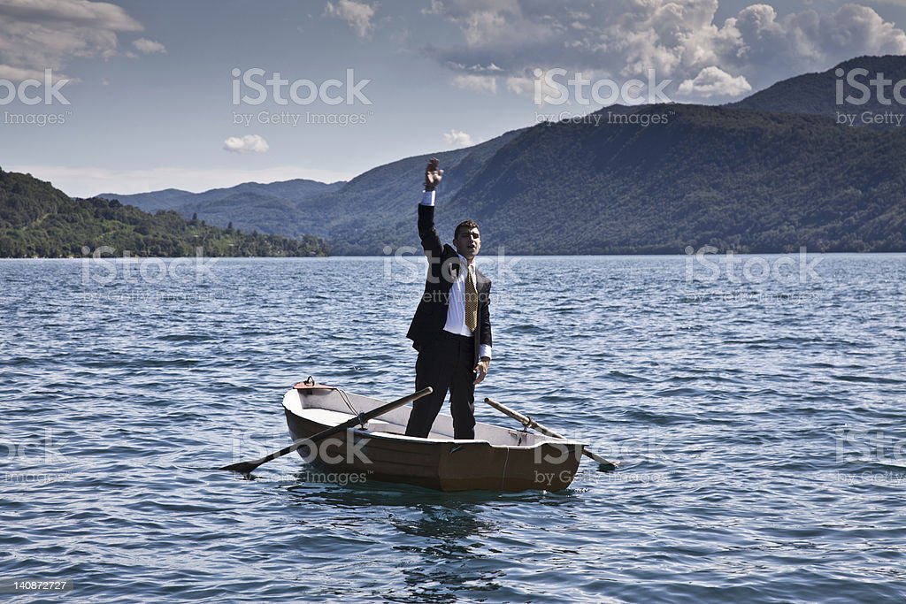 Businessman calling for help in rowboat stock photo