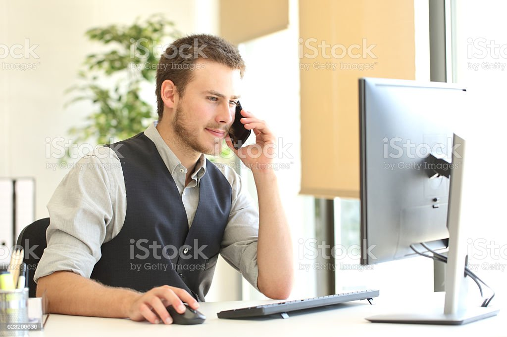 Businessman calling on phone and using a computer stock photo