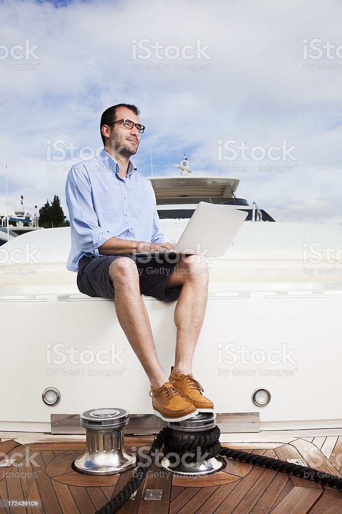 Businessman, Captain of the yacht. Relaxing. Reading e-mails. royalty-free stock photo