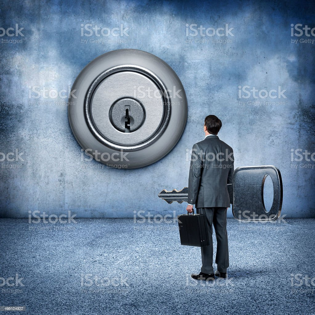Businessman Carriyng A Key Looks Up At Large Lock stock photo