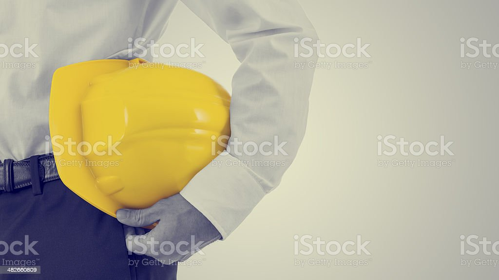 Businessman carrying a yellow hardhat stock photo