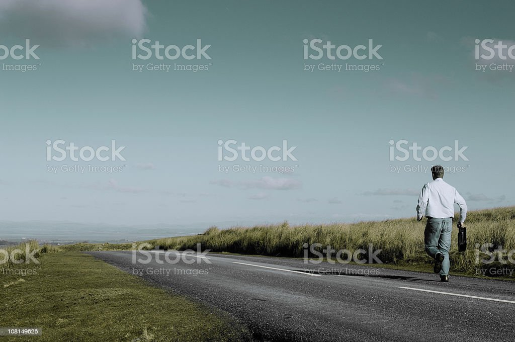 Businessman Carrying Briefcase Running Down Country Road royalty-free stock photo