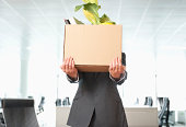 Businessman carrying cardboard box of office items