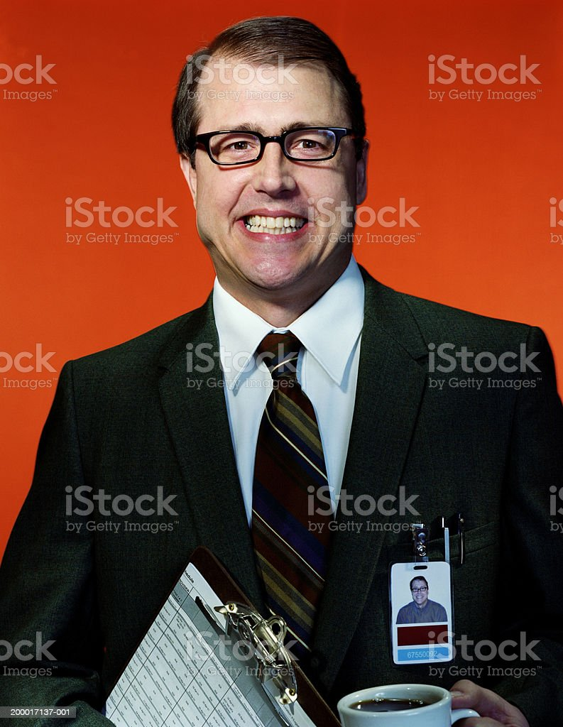Businessman carrying coffee and clipboard, portrait stock photo