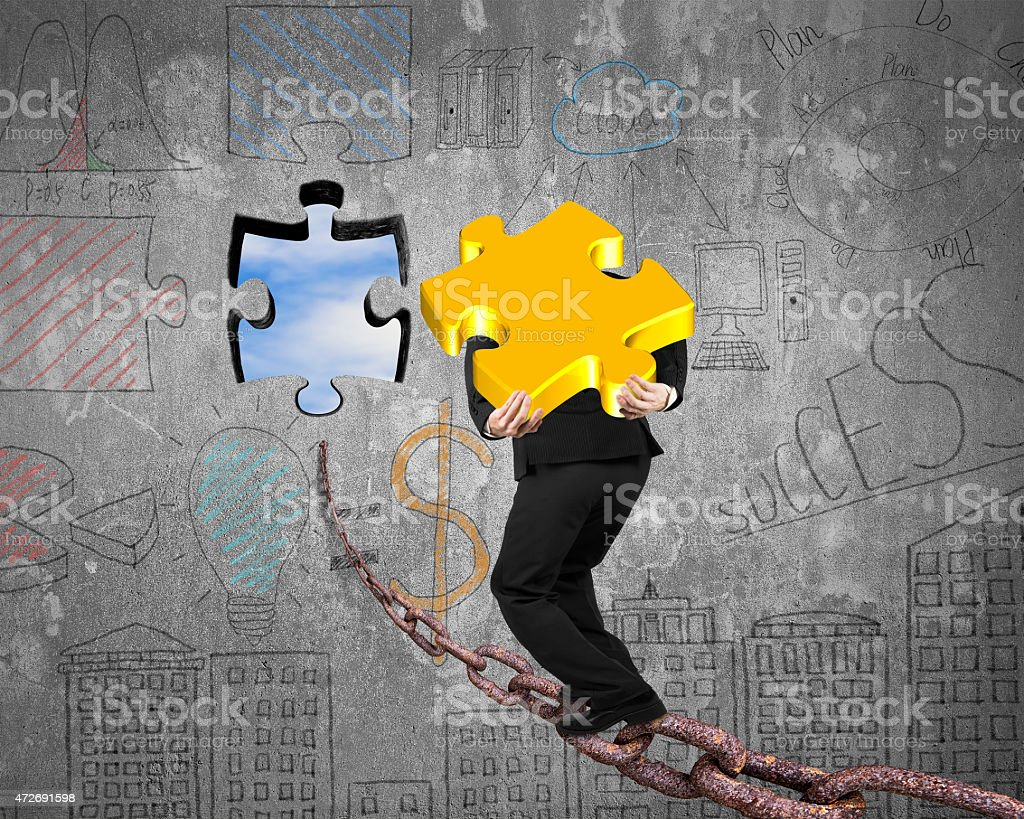 Businessman carrying gold jigsaw puzzle piece toward hole with s stock photo