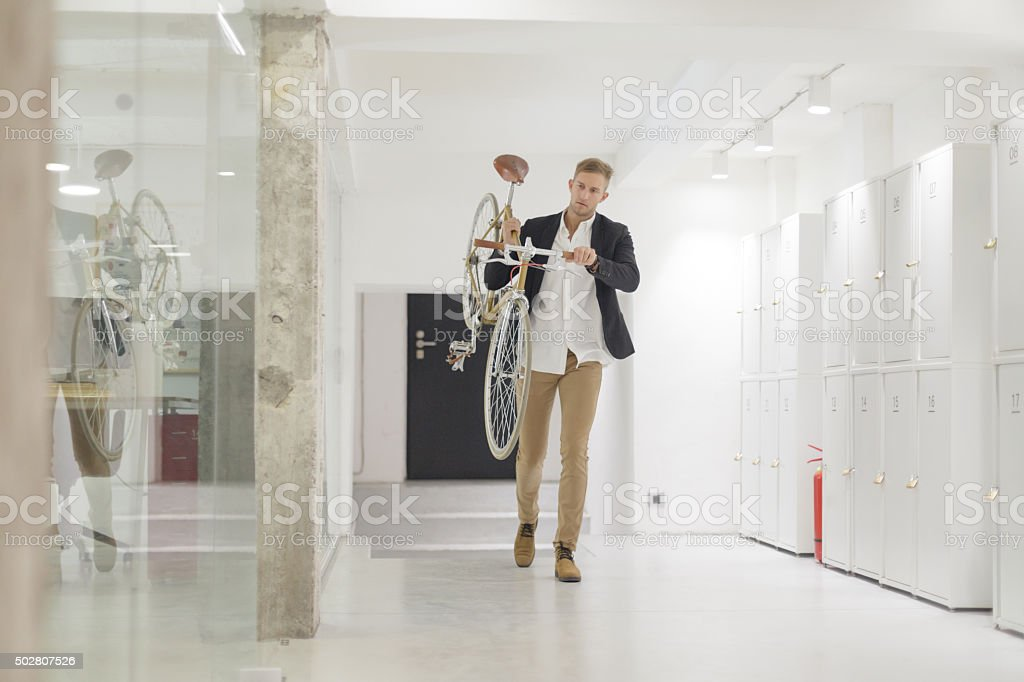 Businessman carrying his bicycle in office stock photo
