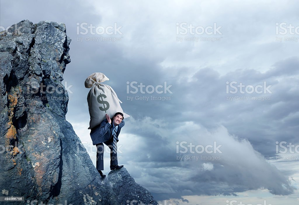 Businessman Carrying Large Money Bag Up A Hill stock photo