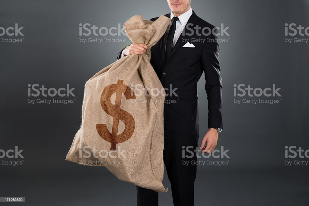 Businessman Carrying Sack With Dollar Sign stock photo