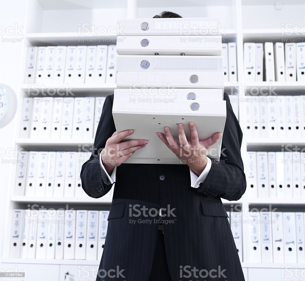 Businessman carrying stack of binders royalty-free stock photo