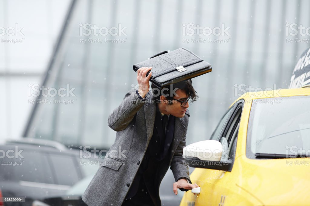 Businessman Catching Taxi in Storm stock photo