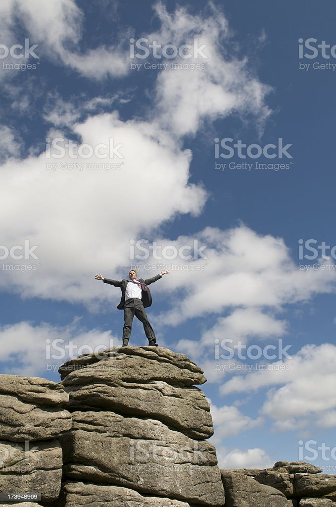 Businessman Celebrates on the top of a Rock royalty-free stock photo