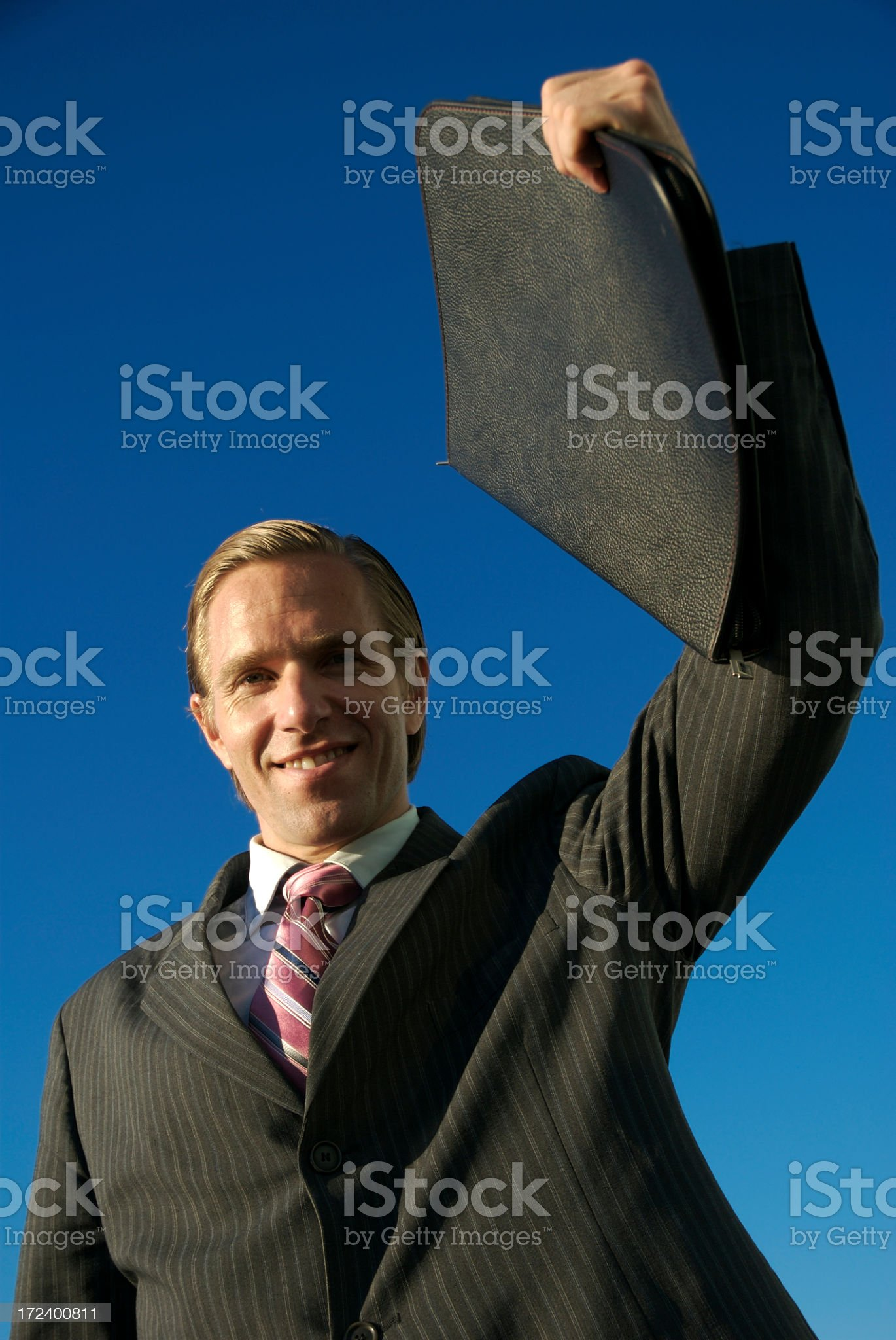 Businessman Celebrates with Portfolio Against Blue Sky royalty-free stock photo