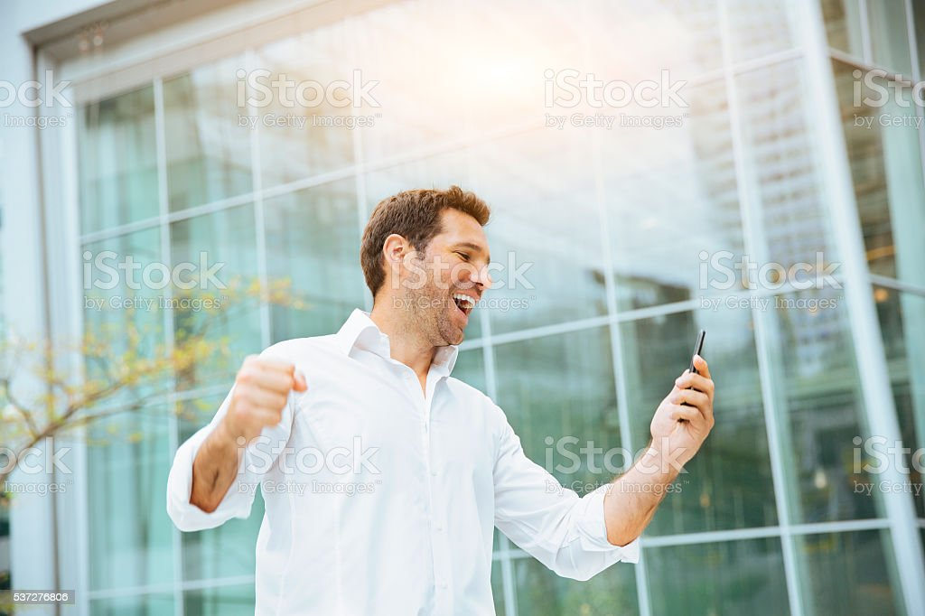 Businessman celebrating his success on smartphone stock photo