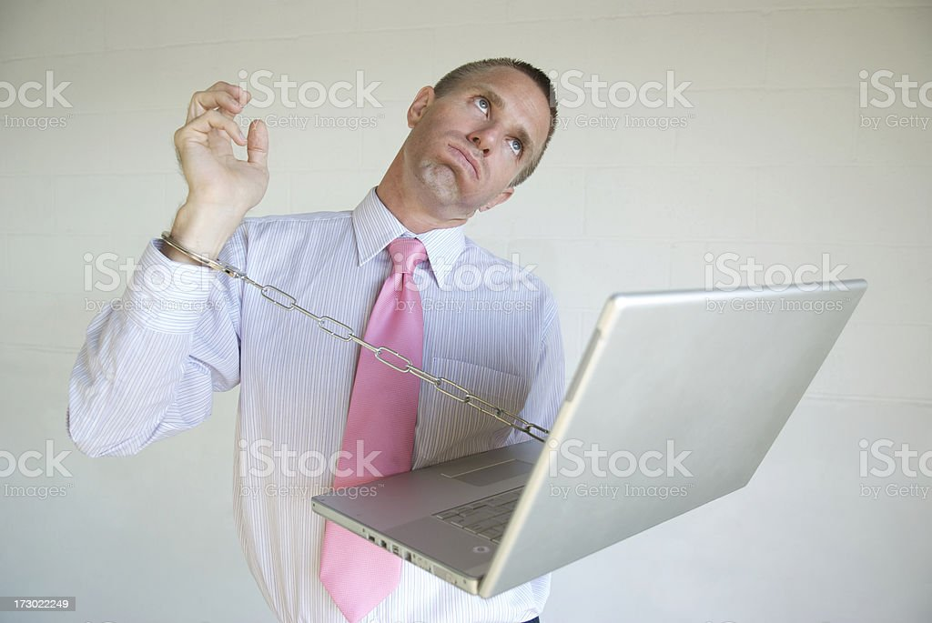 Businessman Chained to Computer Looks Exasperated royalty-free stock photo