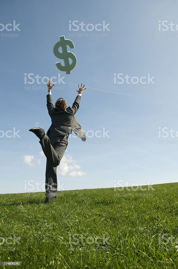 Businessman Chasing Dollars Falling from Sky on Field of Dreams royalty-free stock photo