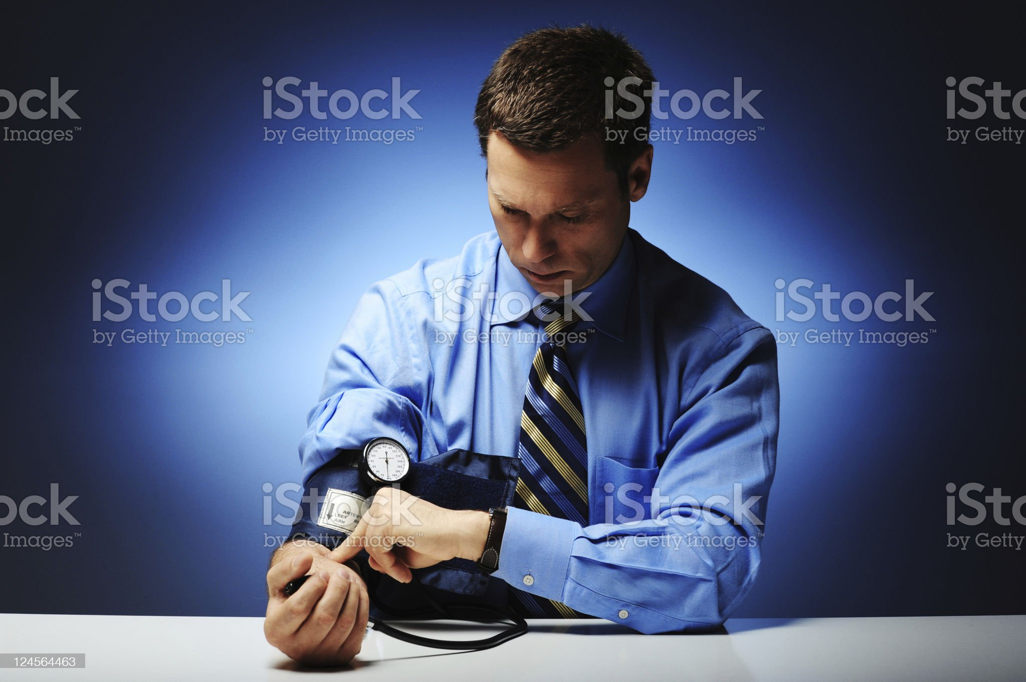 Businessman checking blood pressure with cuff on right arm royalty-free stock photo