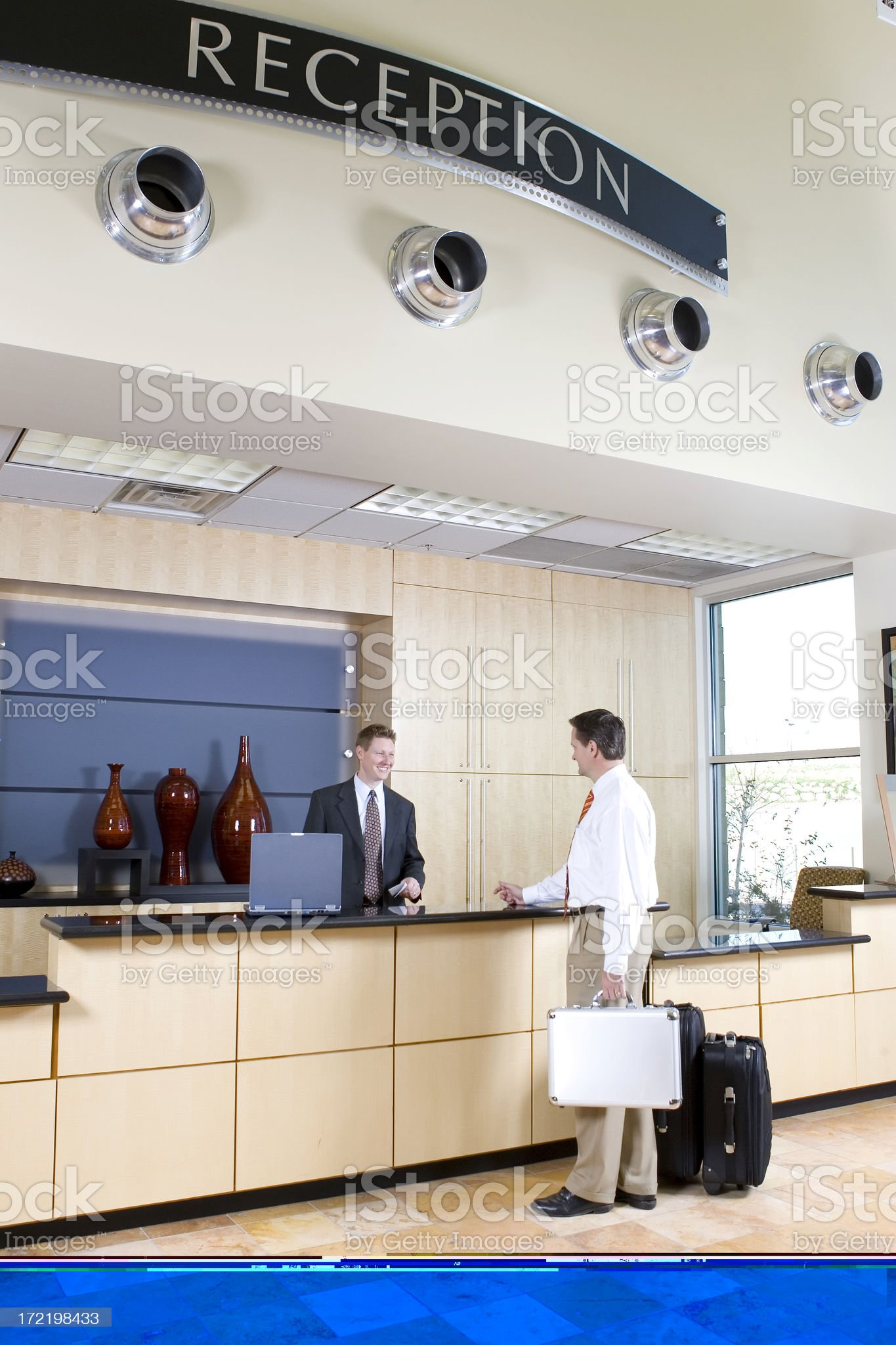 Businessman Checking in at the Reception Desk royalty-free stock photo