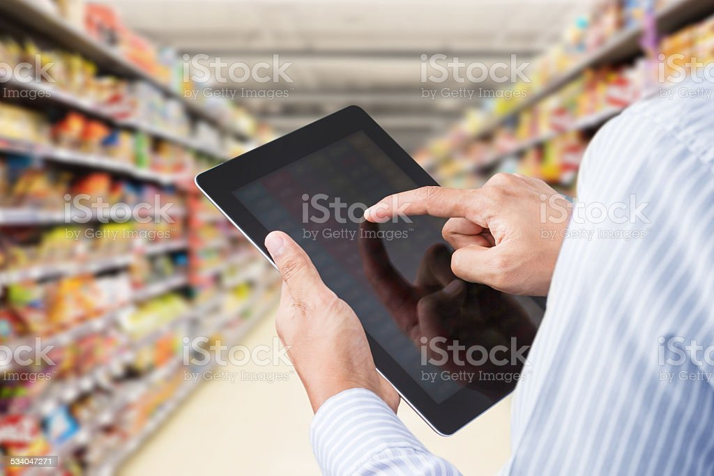 Businessman checking inventory in minimart on touchscreen tablet stock photo