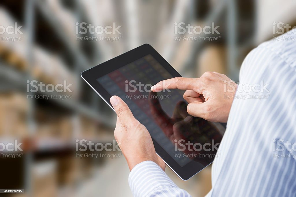 Businessman checking inventory in stock room on touchscreen tablet stock photo
