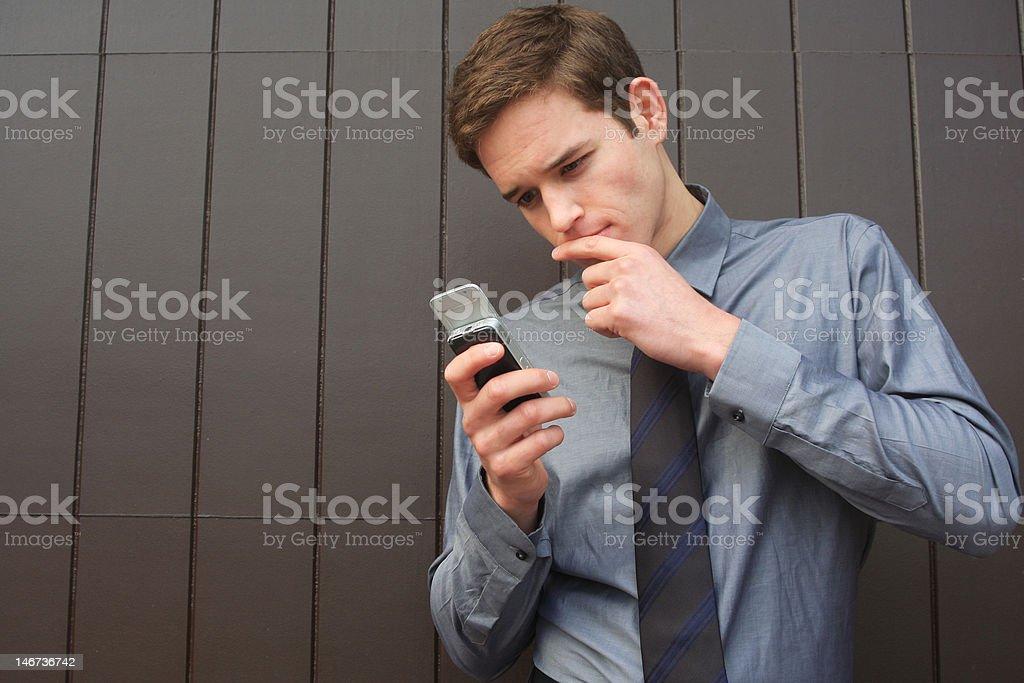 Homme d'affaires vérifiant les messages sur téléphone portable photo libre de droits