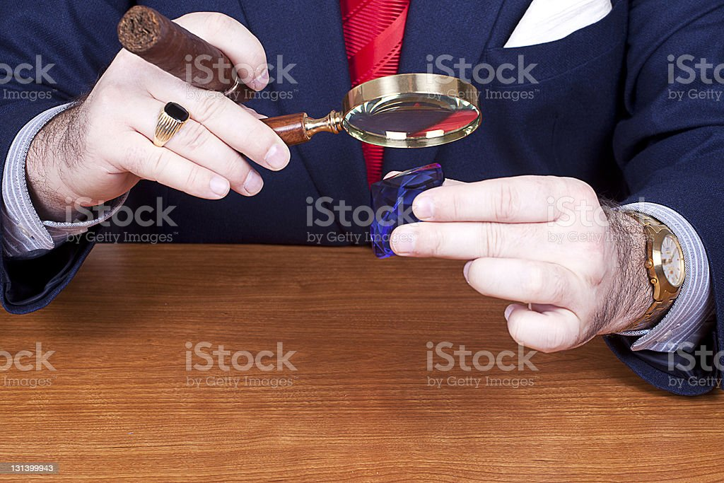 Businessman checking out a diamond. stock photo