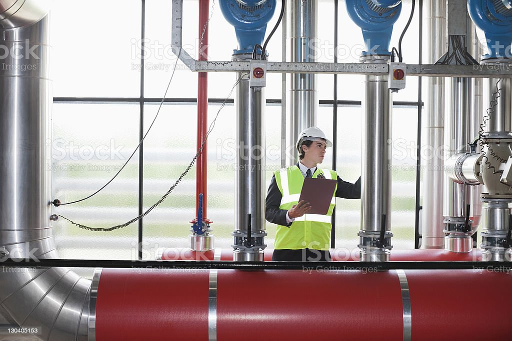 Businessman checking pipes in factory royalty-free stock photo