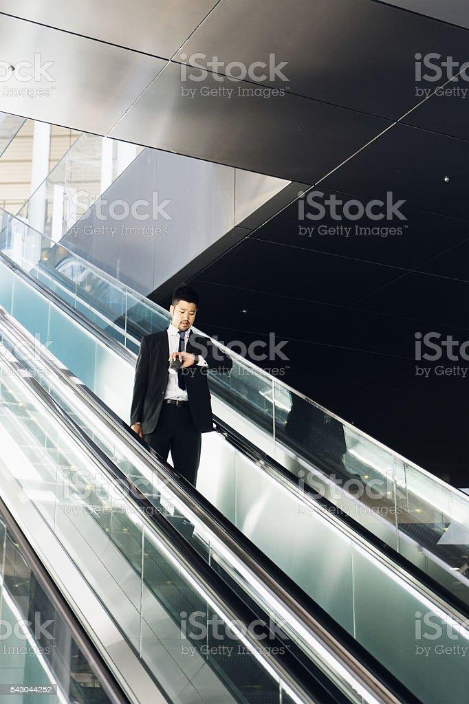 Businessman Checking The Time On Escalators stock photo