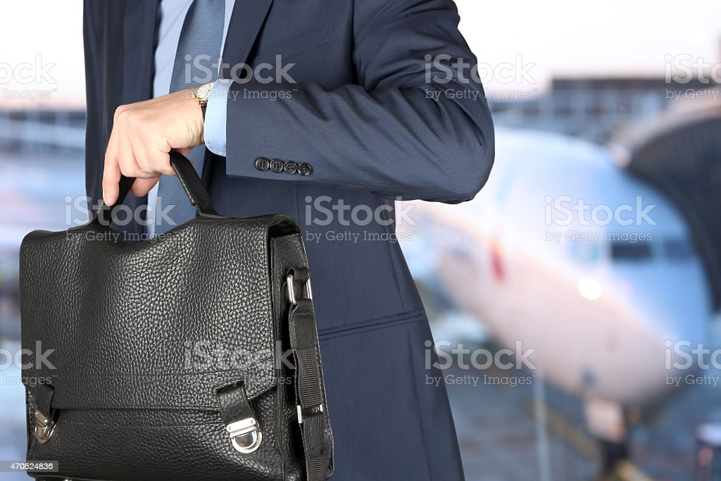 Businessman checking time on his watch. Airplane behind stock photo