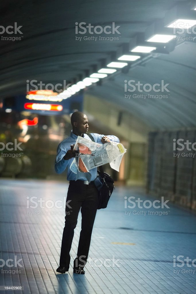 Businessman checking time while struggling with newspaper royalty-free stock photo