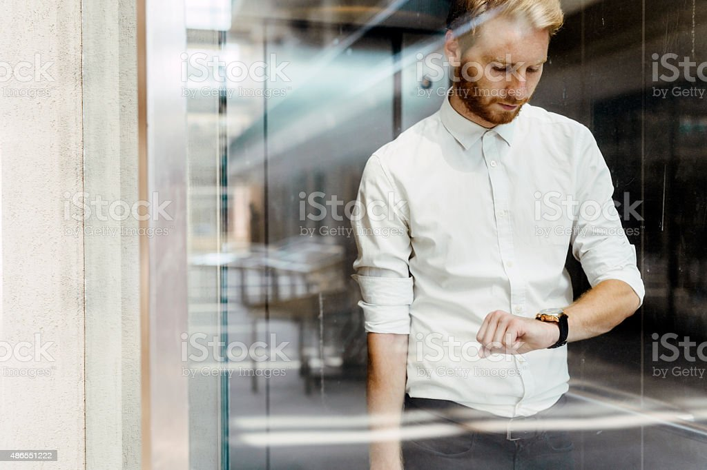 Businessman checking watch while standing in elevator stock photo