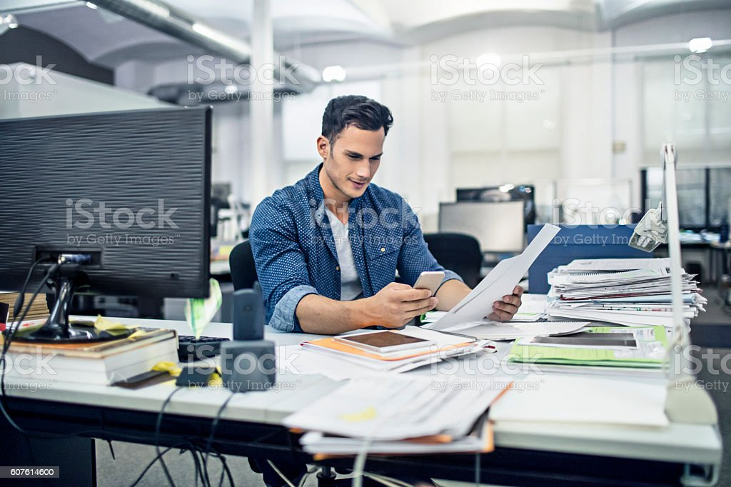 Businessman checks documents while on the mobile phone stock photo