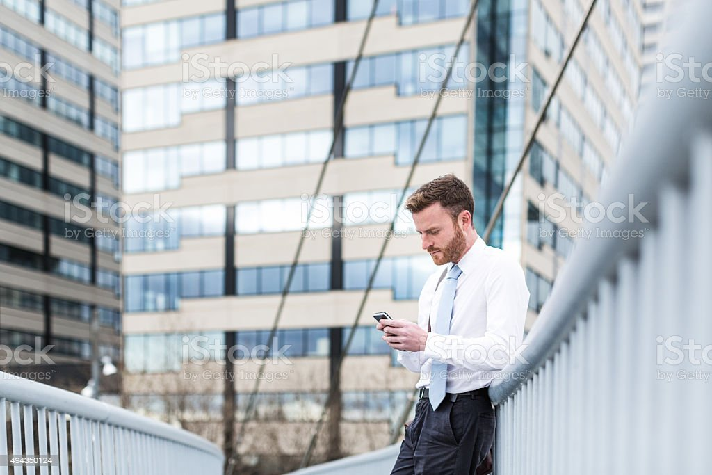 Businessman checks smartphone stock photo