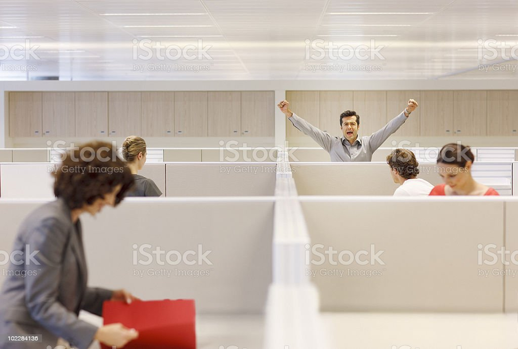 Businessman cheering in cubicle stock photo